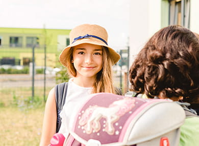 girl wearing a summer hat looking into the camera outside of the school