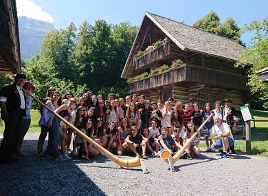 students standing in front of a swiss house, two alphorns in the front