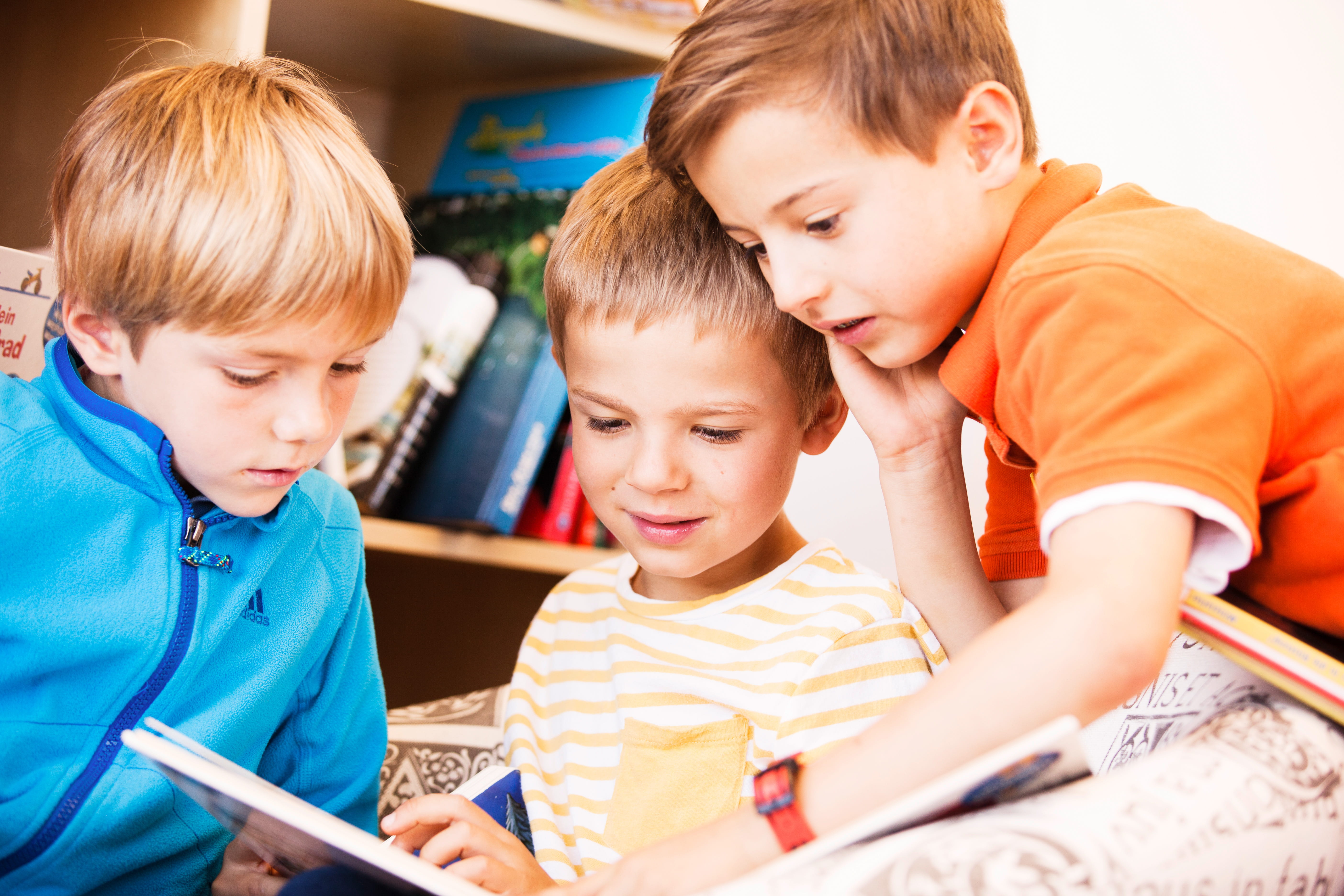 three students reading a book